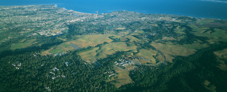 Aerial view of UC Santa Cruz campus with Monterey Bay National Marine Sanctuary and the city of Santa Cruz as backdrop